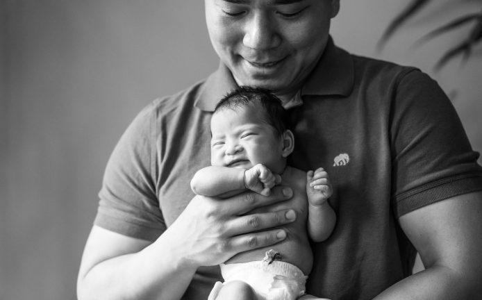 men is holding his newborn daughter