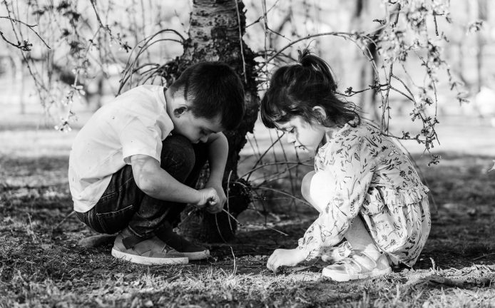 two kids are sitting on the grass and playing